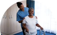 Nurse assisting senior women in walking with walker at nursing home