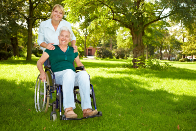 senior in a wheelchair and caregiver smiling