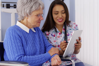 caregiver and senior woman looking at the tablet
